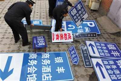 """2009年12月8日,北京相关部门在整治行动中,拆除""""山寨指路牌""""。图/视觉中国"""