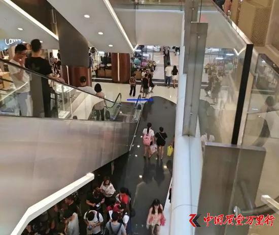 魏姐和她的一位亲戚(蓝线处)正在向路人兜售喜茶,身后10米电梯下方便是喜茶排队处