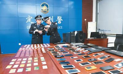 山东省菏泽市定陶区公安局反诈骗中心民警正在对收缴的赃物进行清点。   朱建英摄(人民图片)