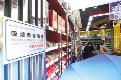 7月4日,深圳市坪山区马峦市场监管所执法人员在万众百货的烟酒摊位前执法。本版图片/深圳市卫生计生委